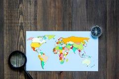 Viaje del planeamiento Mapa del mundo y compás en copyspace de madera de la opinión superior del fondo de la tabla Fotos de archivo
