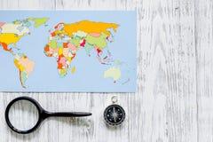 Viaje del planeamiento Mapa del mundo y compás en copyspace de madera de la opinión superior del fondo de la tabla Foto de archivo