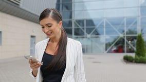 Viaje del trabajo Mujer de negocios con el teléfono y la maleta cerca del aeropuerto almacen de video