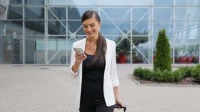 Viaje del trabajo Mujer de negocios con el teléfono y la maleta cerca del aeropuerto metrajes