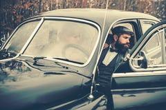 Viaje del viaje y de negocios o el caminar del tirón Hombre barbudo y mujer atractiva en coche Acompañamiento de muchacha por seg imagenes de archivo