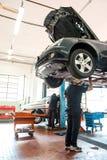 Viaje en automóvili al mecánico que trabaja en un coche en un alzamiento foto de archivo