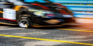Viaje en automóvili competir con de coche deportivo en la carretera de asfalto con la cerca azul y la línea amarilla señal de trá Fotografía de archivo libre de regalías