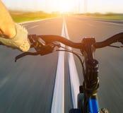 Viaje en bicicleta a lo largo de la velocidad de la puesta del sol del verano del asfalto del camino Fotos de archivo libres de regalías