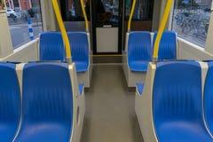 Viaje en tranvía dentro, interior del transporte de la ciudad con las manijas azules del amarillo de los asientos imagen de archivo