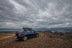 Viaje en un coche azul hermoso en las montañas Imágenes de archivo libres de regalías