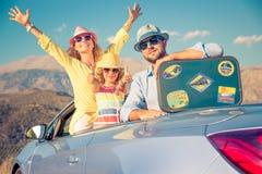Viaje feliz de la familia en coche en las montañas