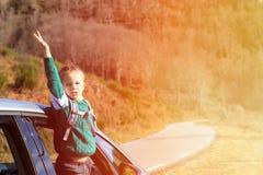 Viaje feliz del niño pequeño en coche en naturaleza del otoño Imagenes de archivo