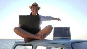 Viaje, mujer joven que se sienta en el coche del vintage en luz del sol usando accionado por la batería para el ordenador en la p