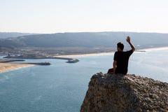 Viaje para el concepto de la vida El hombre se está sentando en la roca, mirando en la distancia Foto de archivo