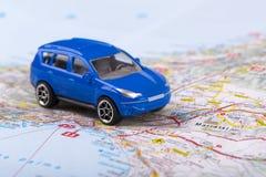 Viaje por carretera, pequeño coche del juguete en mapa Imágenes de archivo libres de regalías