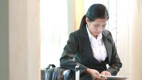 Viaje que espera de la mujer de negocios para y tableta con metrajes