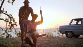 Viaje romántico de los pares jovenes para apuntalar el río, muchacha con el varón en la oscilación en el mar de la costa en el oc almacen de video