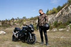Viaje a una motocicleta con una carrera Un motorista con un casco en sus manos mira una motocicleta foto de archivo
