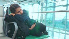 Viajero adolescente de la muchacha cansada que duerme en el aeropuerto que espera el banco plano de las puertas de salida con tod almacen de metraje de vídeo