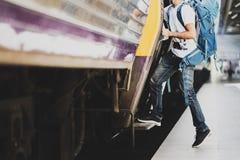 Viajero asiático joven con la mochila en el ferrocarril, viajero que se sostiene y que intensifica a un tren con la mochila para  fotos de archivo libres de regalías