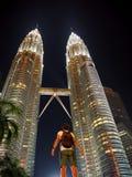 Viajero asombroso que mira para arriba a las torres gemelas iluminadas de Petronas en Kuala Lumpur foto de archivo libre de regalías