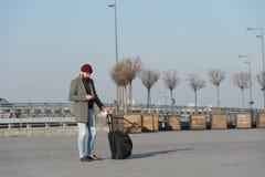 Viajero con el transporte que espera de la maleta al ferrocarril del aeropuerto Aliste para viajar Lleve el bolso del viaje Negoc imagen de archivo libre de regalías