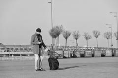 Viajero con el transporte que espera de la maleta al ferrocarril del aeropuerto Aliste para viajar Lleve el bolso del viaje Negoc foto de archivo