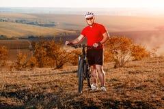 Viajero con la mochila que monta la bici en el otoño hermoso Foto de archivo libre de regalías