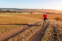 Viajero con la mochila que monta la bici en el otoño hermoso Foto de archivo