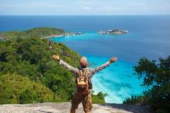 Viajero con la mochila que se coloca en las rocas foto de archivo libre de regalías