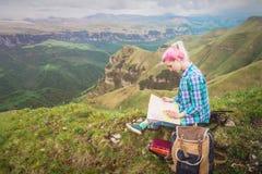 Viajero de la muchacha con el pelo multicolor que se sienta en tarjeta y la tenencia de la lectura de la naturaleza un compás a d fotos de archivo libres de regalías