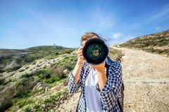 Viajero de la muchacha con una cámara a disposición, contra un verano hermoso imagen de archivo