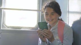 Viajero de la muchacha del adolescente con una mochila que se sienta en las mochilas de los bolsos en la ventana del coche con un almacen de metraje de vídeo