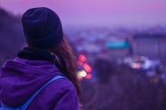 Viajero de la muchacha del inconformista que mira paisaje urbano de la tarde del invierno, el cielo púrpura y luces borrosas de l Foto de archivo