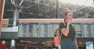 Viajero de la muchacha en el aeropuerto a hablar en un tel?fono m?vil almacen de video