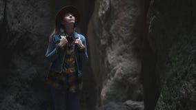 Viajero de la muchacha en una cueva o un barranco Ella está llevando un sombrero y una chaqueta y tiene una mochila Explora una c almacen de metraje de vídeo