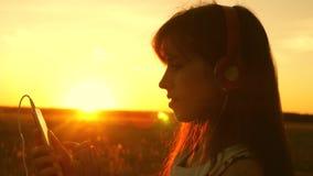 Viajero de la muchacha que escucha la música en smartphone en rayos de una puesta del sol hermosa de la primavera chica joven con metrajes