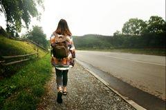 Viajero de la mujer con la mochila que camina abajo del camino en montañas, Fotos de archivo libres de regalías