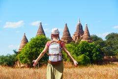 Viajero de la mujer con una mochila que camina a través de campo a los stupas antiguos fotos de archivo