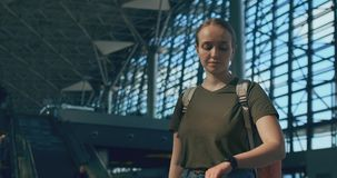 Viajero de la mujer en el aeropuerto que mira las marcador-salidas que buscan su vuelo almacen de video