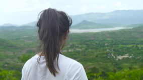 Viajero de la mujer en el pico de montaña que mira en paisaje en bosque tropical verde desde arriba Morenita conmovedora de la mu almacen de metraje de vídeo