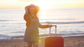 Viajero de la mujer joven con una maleta en la playa en puesta del sol almacen de metraje de vídeo