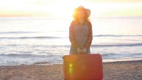 Viajero de la mujer joven con una maleta en la playa en puesta del sol almacen de video