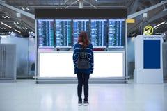 Viajero de la mujer joven en el aeropuerto internacional que mira al tablero de la información del vuelo foto de archivo
