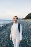 Viajero de la mujer joven en una ropa blanca que se coloca en la playa Imágenes de archivo libres de regalías