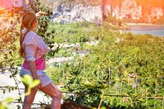 Viajero de la mujer que disfruta de la visión y que mira lejos en selvas y el mar del top de la colina fotos de archivo