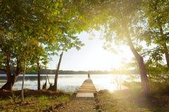 Viajero de la mujer que se coloca en el embarcadero, mirando al abo hermoso de la puesta del sol imagen de archivo