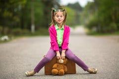 Viajero de la niña en ropa brillante en el camino con una maleta y un oso de peluche Feliz Fotos de archivo