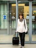 Viajero de la señora que sale de la taquilla Fotografía de archivo