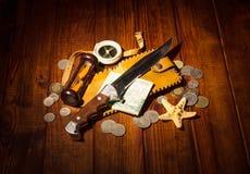 Viajero de los accesorios: compás, reloj de arena, cuchillo, dinero en la madera de la oscuridad del fondo Imagen de archivo
