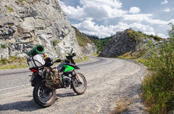 Viajero del enduro de la motocicleta con las maletas que se colocan en la trayectoria de la carretera de asfalto en un paso del m Foto de archivo