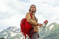 Viajero del hombre con el mapa y la mochila roja que buscan la ubicación al aire libre con las montañas rocosas en fondo imagen de archivo libre de regalías