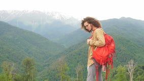 Viajero del hombre con la mochila roja que mira la cámara al aire libre con las montañas rocosas en fondo almacen de metraje de vídeo