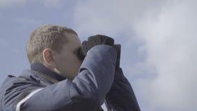 Viajero del hombre joven que usa los prismáticos cerca para arriba El cielo se nubla la cámara lenta del fondo almacen de video